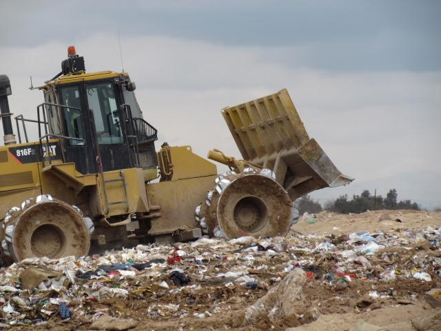 Landfill-tractor covering waste
